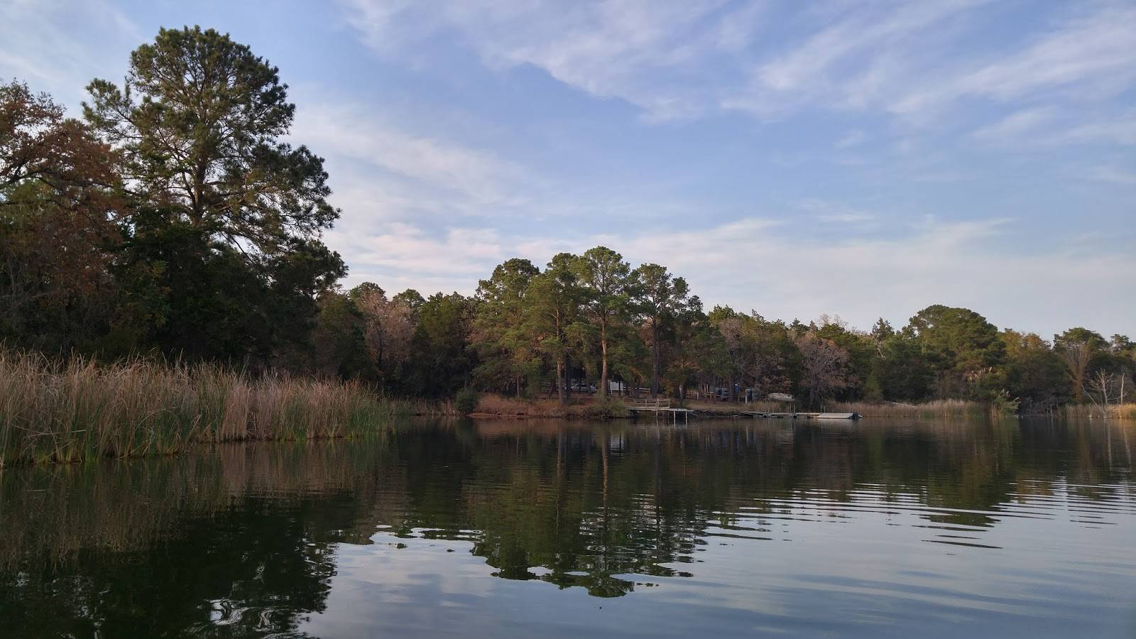 Kayak Fishing Lake Bastrop Shoreline with trees and beautiful calm water.